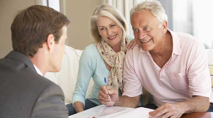 Senior couple learning about life settlement broker services